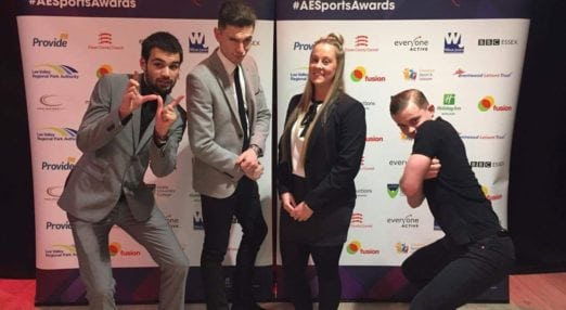 4 Coach Core apprentices in front of a step&repeat board