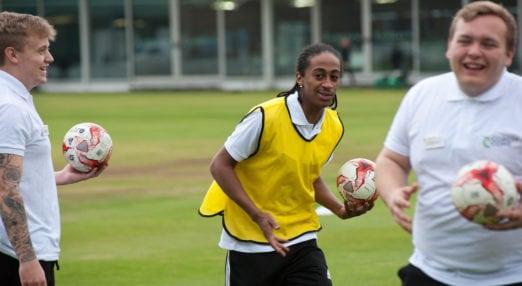 Coach Core apprentice in field leading training session