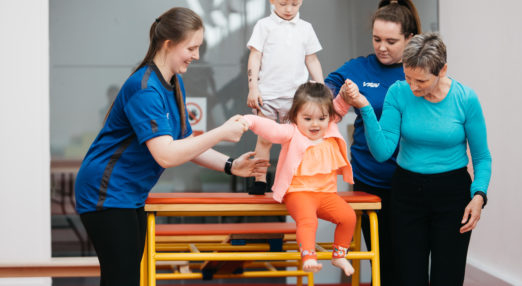 Two Coach Core apprentices help a child over gym equipment
