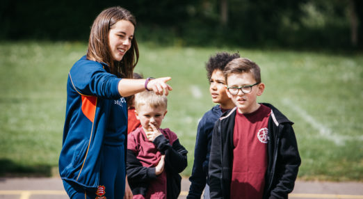 Coach Core apprentice leads training session for children in playground