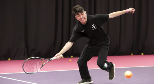 Coach Core apprentice playing tennis