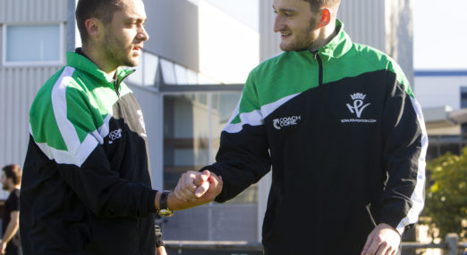 Two Coach Core apprentices shake hands