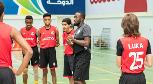 Coach Core apprentice leads a sports session in a hall