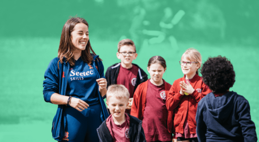 a young woman coach stands laughing with a group of children
