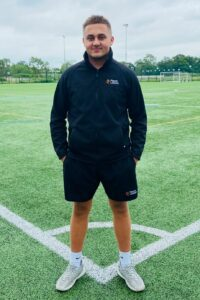 Apprentice stands on pitch